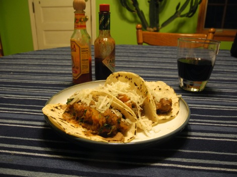 Pumpkin-turkey tacos on a plate with bottles of hot sauce in the background