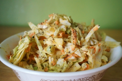 Classic mustard coleslaw in a shallow ceramic bowl, with extra ground pepper on top