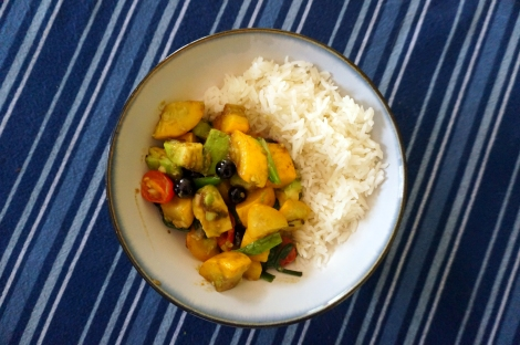 An overhead shot of a bowl of colorful summer squash saute; the saute sits in the lower left, with a mound of rice in the upper right