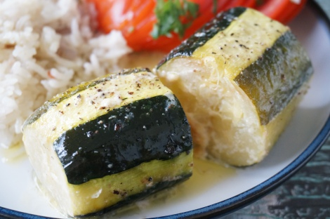 Two pieces of simple baked zucchini à la française, plated, with glimpses of tomatoes and rice in the background.