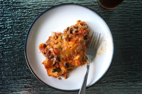 A serving of Sweet potato-black bean enchiladas sits on a small plate, with one bite already taken and a fork lying where the bite had been.
