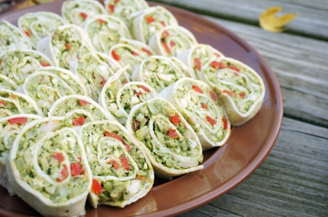 Cilantro chicken pinwheels: closeup showing finely chopped, green-tinted chicken, studded with tiny squares of red pepper, all within a spiral of flour tortilla