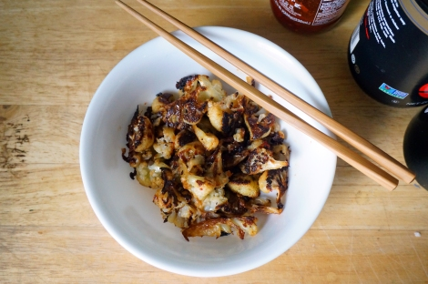 A small white bowl of spicy roasted cauliflower, with a pair of chopsticks balanced on its edge. In the background we see the edges of bottles of chile paste, soy sauce, and sesame oil.