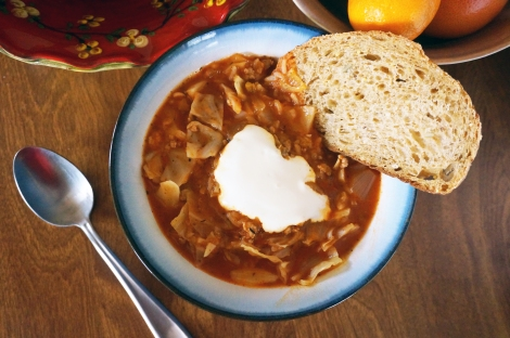 Stuffed cabbage soup, in an overhead shot. A slice of multigrain bread rests on the rim of the bowl, and a big dollop of sour cream floats in the middle of the brick-red soup. Bowls of produce peek in at the edges of the image.