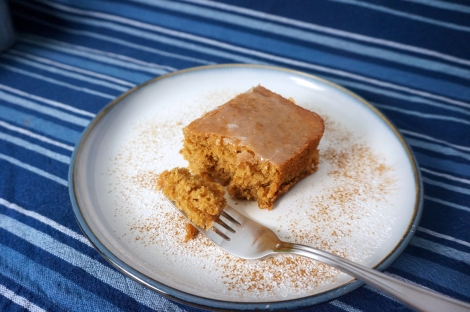 A square of Cola cake sits on a plate dusted with cinnamon and powdered sugar. A forkful has been taken off, and sits on the fork in the foreground.