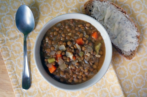 A bowl of basic lentil soup sits on a yellow napkin, along with a shiny spoon and a piece of thickly buttered bread