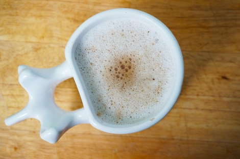 Cardamom coffee in a mug whose handle is modeled after a human vertebra. A layer of bubbly froth covers the top of the mug, with a warm brown smudge in the center where the coffee was poured.