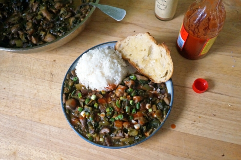 A plate of smothered mushrooms with spinach, accompanied by white rice and buttered bread, garnished with chopped green onions and hot sauce. A skillet of the dish rests at the edge of the picture, and bottles of Creole seasoning and hot sauce sit near the plate