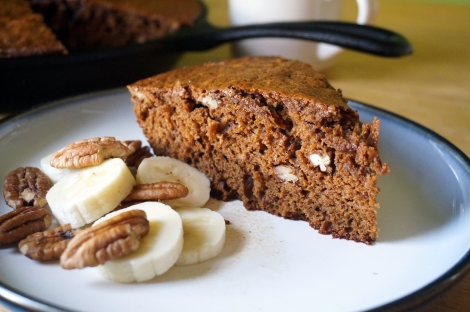 A wedge of rum & coffee banana bread sits on a small white plate, accompanied by a little pile of banana slices and pecan halves. In the background, an ivory coffee mug and a black cast iron skillet, which holds the remainder of the bread.