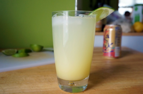 A glass of ginger beer, garnished with a wedge of lime at a jaunty angle, sits on a wooden countertop. In the background, wedges of lime on a cutting board, and a pink and orange can of La Croix sparkling water.