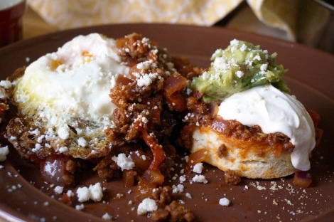 Closeup on masa harina biscuits with spicy chorizo topping. Two halves of a biscuit are each covered in a generous scoop of chorizo topping that spills over onto the plate; the left half is topped with a fried egg, and the right with sour cream and guacamole; crumbled cotija cheese is sprinkled over the whole plate.