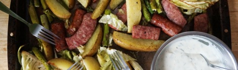 A dark brown rimmed baking sheet filled with pan-roasted asparagus, cabbage, potato, and smoked sausage, with a big bowl of herb-flecked yogurt sauce in the corner, and a whole bunch of forks laid around, ready to dig in