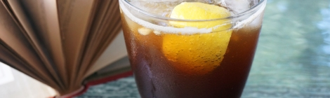 A simple rocks glass sits on a glass tabletop, filled with a fizzing, dark brown, iced drink with a wedge of lemon floating at the near side of the glass. Behind the glass, a book lies open on the table, pages spreading like a fan.