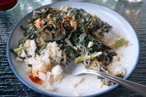 A plate of collards with coconut and peanut butter, drizzled with hot sauce, sits partially eaten, a fork nestled among the rice grains and dark green leaves.