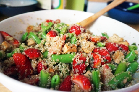 Strawberry-snap pea salad with quinoa and tofu, a jumble of textures on colors in a large white bowl with a wooden spoon stirring it all up
