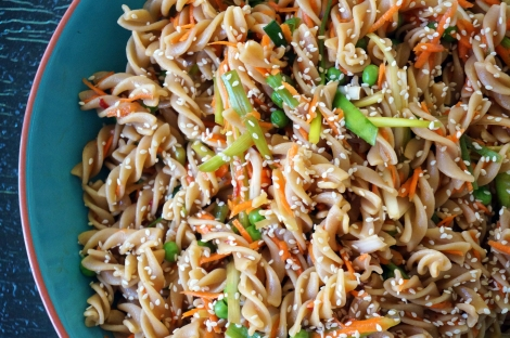 Citrus & soy pasta salad piled in a light blue bowl, tangles of bright orange carrot and pale green scallions curling around the spirals of whole wheat rotini scattered with sesame seeds