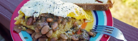 A thick slice of cornbread, covered in beans and topped with a fried egg, sits on a brightly-colored plate on a porch rail.
