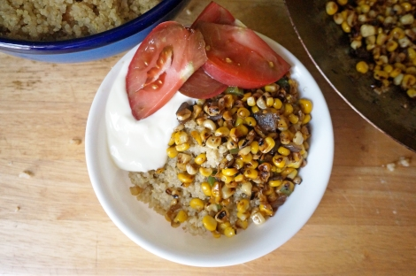 A big scoop of quinoa in a white bowl, topped with bright yellow corn spotted with brown and dressed with a dollop of yogurt and a few slices of bright red tomato. At the edges of the picture, a serving bowl of quinoa and a wok full of more charred corn.