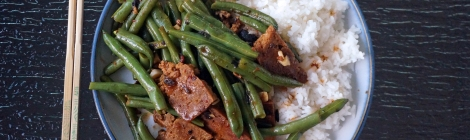 On a glass table, a blue-rimmed plate, with a pair of chopsticks laid to the left. On the plate, a mound of fluffy white rice, half-covered with wrinkled green beans and slices of dark brown pan-crisped seitan, all dressed lightly in a brown sauce and flecked with black, beige, and red-brown bits of seasoning.
