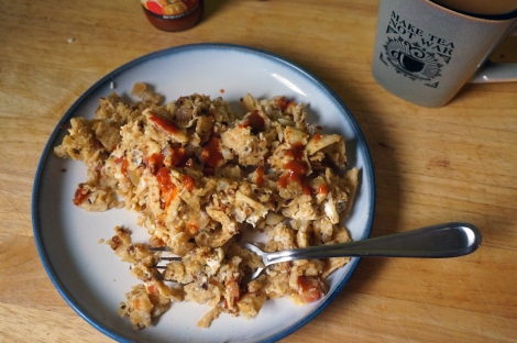 A plate of migas, crumbled tortilla chips softened by scrambling in eggs, with a stainless steel fork buried in them. Dashes of bright red hot sauce dot the dish, and a mug of coffee stands at the ready plateside.