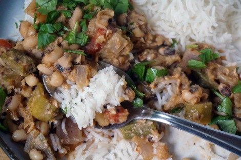 Closeup on a spoon of black-eyed pea and okra curry, with rice, sitting in the midst of the larger plateful, the delicate white grains of rice contrasting with the hearty thickness of brown, red, olive, and green curry ingredients.