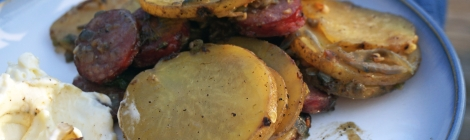 Closeup on a plate of fried potatoes, pale yellow discs of potato studded with brick-red rounds of sausage and soft shreds of meltingly soft jalapeño and onion. In the foreground, blurry, a bite potato and sausage speared on a fork, touched with mayonnaise from a thick dollop in the corner of the frame.