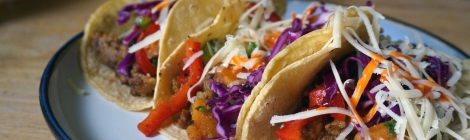 Sweet potato tacos with marinated peppers and cabbage, three of them, nestled together on a plate, garnished with white shredded cheese and bright orange hot sauce.