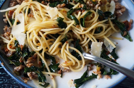 A fork lies amidst a tangle of spaghetti, tines completely hidden. Ribbons of kale, small nubbins of sausage, and shards of Parmesan cheese punctuate the plate.