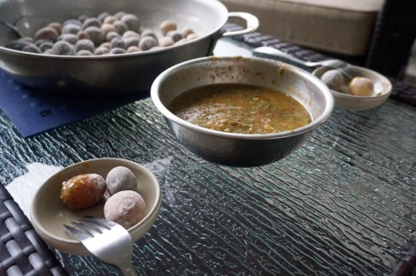Three salt-crusted new potatoes sit in a tiny dish in the foreground; behind them a good-sized bowl of peach-basil dipping sauce. In the background, a large two-handled pan full of more potatoes.