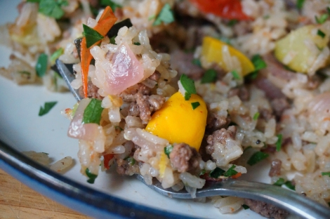 A bite of pilaf on a fork in close-up, bits of ground beef, onion, parsley, and tomato scattered among the grains of rice, and a bright yellow chunk of squash dead center.