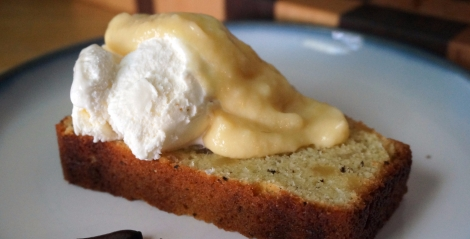 A slice of pepper-ginger pound cake sits on a small plate, topped with a scoop of vanilla ice cream and a light yellow cascade of pawpaw puree. Two pawpaw seeds sit on the plate as garnish.