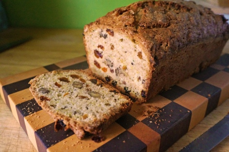 A slice of zucchini bread lies next to the rest of the loaf, all resting on a checkerboard wooden cutting block, which itself contrasts with the blonde wood counter and a bright green painted wall.