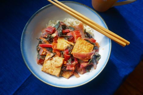 Overhead shot of a bowl of tofu and chard, with a pair of twisted-bamboo chopsticks resting on one edge, the bowl centered on a dark blue cloth.