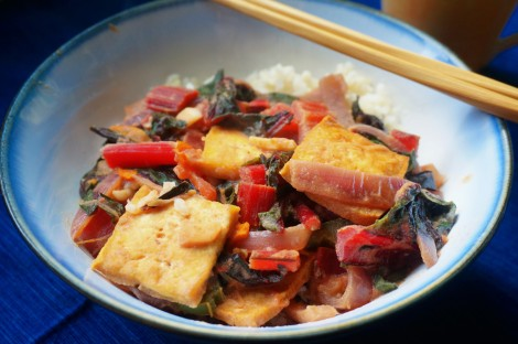 Closeup on a bowl of tofu and chard, the bright red of the chard stems standing out against the rich gold-brown of the fried tofu squares and the dark green of the chard leaves.